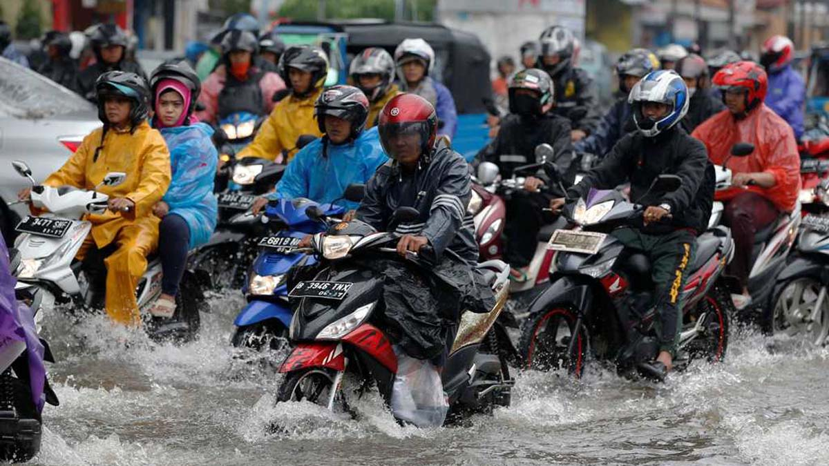 Motorists ride their motorcycles through a flooded intersection